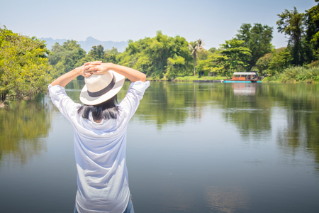 Asian woman wear hat and white shirt with standing on wooden bridge. She looking forward to river with put her hands on head and she has feeling relax and happiness.
