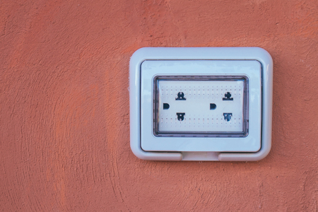 Empty white dual electric outlet with plastic waterproof setup on brown clay wall. (Selective focus)