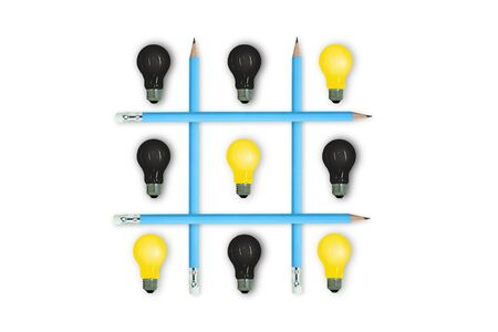 Business Competition and Idea Concept : Yellow and Black light bulbs in OX game isolated on white background. Banco de Imagens
