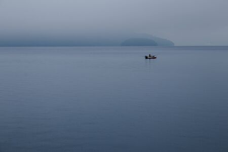 Fisherman fishing in speed boat, The boat floating in Toya Lake surrounded with fog in cloudy day at Hokkaido, Japan.