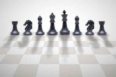 Concetto di concorrenza aziendale: pezzi degli scacchi in legno in piedi sulla scacchiera. Archivio Fotografico