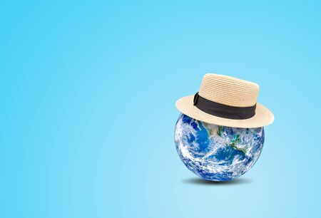 Summer Vacation and Holiday Concept : Blue planet earth globe wear weave hat on blue background.