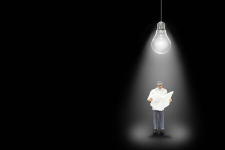 Business Idea Concept : Light bulb shading light to businessman that reading newspaper in black background.