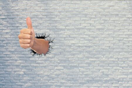 Showing hand thumbs up signs through concrete wall. Stok Fotoğraf