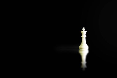 Business Leadership Concept : White King chess piece standing on floor with shadow shading on floor.