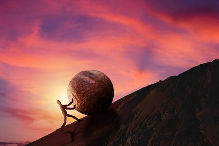 Business Challenge and Success Concept : Wooden figure pushing large stone uphill to top of mountain with sunset and beautiful sky in background.