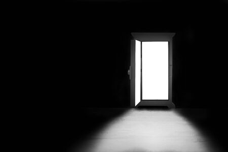Abstract image of Light shining through opened door in dark room. Stock fotó