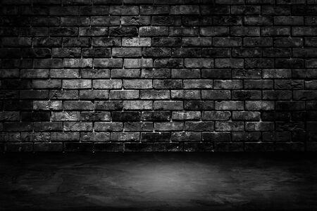 Immagine astratta del muro di mattoni nero della stanza oscura di architettura con il pavimento di cemento.