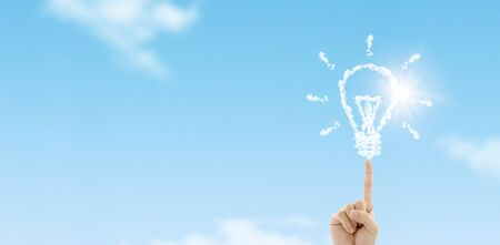 Business Idea Concept : Fingertip touch white clouds in light bulb shape with blue sky in background.