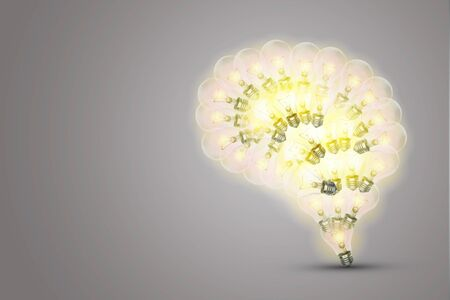 Business Idea Concept : Bright yellow light bulb in brain shape with grey background.