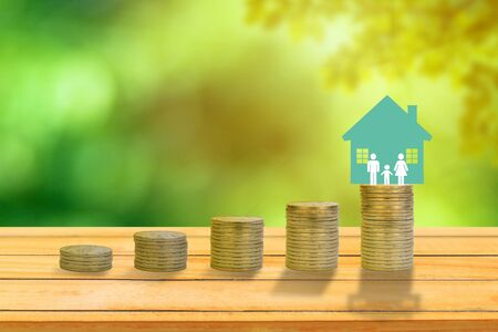 Business Investment Concept : Home and family icon put on stack of coins with green natural and sunlight in background. Stockfoto