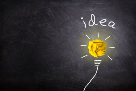 Business Idea Concept : Yellow crumpled paper ball light bulb lighting grow around on chalkboard.