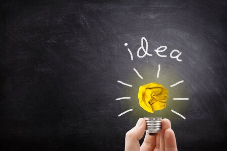 Business Idea Concept : Hand holding yellow crumpled paper ball light bulb lighting grow around on chalkboard.