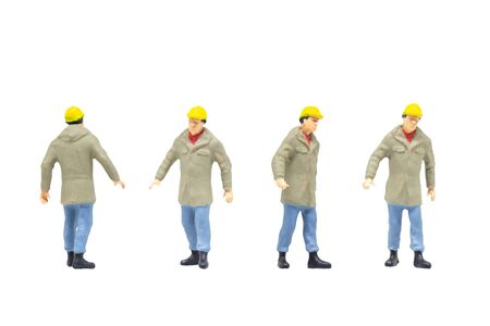 Miniature figurine character as worker wearing protective clothes and posing in posture isolated on white background.