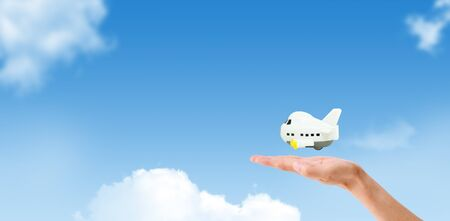Travel Insurance Concept : Hand holding and take care white airplane model toy flying in blue sky.