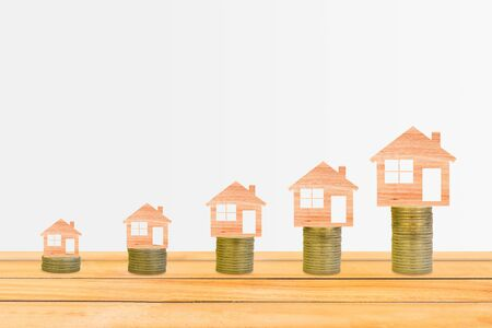 Business Investment for Real Estate Concept : Wooden house or home icons on stack of coins. Stock Photo