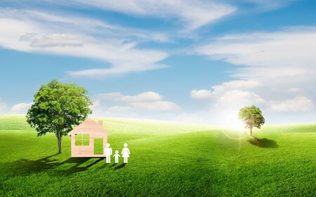 Home with family icons and green green trees locate on grass natural meadow field in little hill with white clouds and blue sky in summer seasonal. Stock Photo