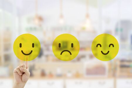 Customer Feedback Concept : Hand pressing smile emotion icons for giving best service ranking with blurred front view of cafe restaurant or coffee shop in the hotel.