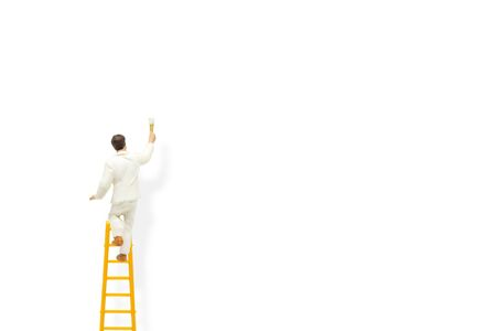 Miniature figurine character as painter standing on wooden ladder and painting white wall with paint tools.