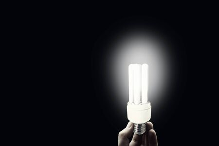 Business Idea Concept : Hand holding light bulb that light growing in dark room.