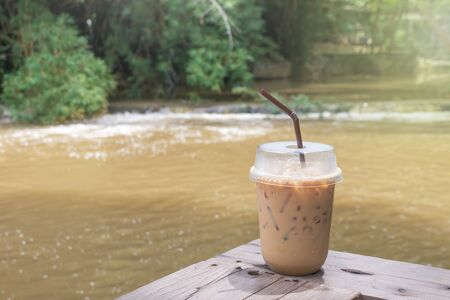 Ice coffee and straw in plastic glass on wooden table with water stream and green trees in background. Stock Photo