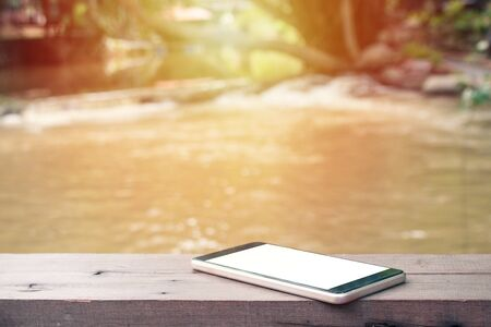 Old black smartphone and white screen on wooden table with water stream and sunlight in background. Stock Photo