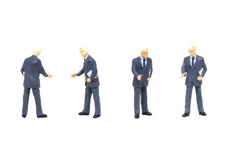 Miniature figurine character as businessman standing and working in posture isolated on white background. Stock Photo