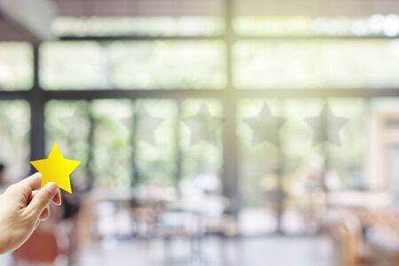 Concetto di feedback del cliente: tenere la mano e dare una stella gialla per il miglior servizio in classifica con un bar ristorante sfocato o una caffetteria nell'hotel.