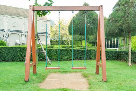 Metal swings hanging on chain place on green grass meadow field in the playground.