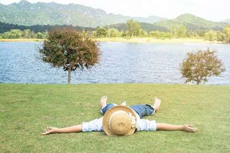 Little Asian girl wear weave hat and laying relax on green grass meadow field nearly lake with mountain in background. Stock Photo