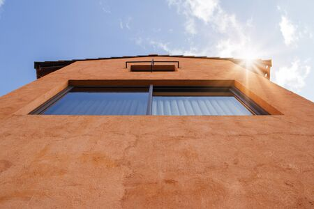 Uprisen angle view of resident with orange clay wall and blue sky in background.