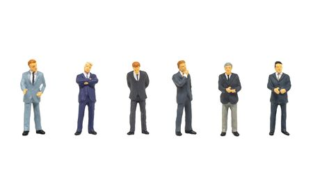 Miniature figurine character as businessman standing and working in posture isolated on white background.