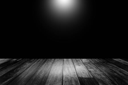 Abstract Black and White image of Empty space studio room of wooden table and spotlight.