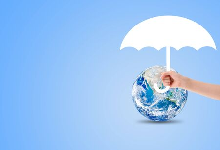 Ecology, Pollution and Environment Concept :  holding white umbrella to protect blue planet earth. Stock Photo