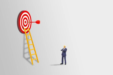 Business Planning and Marketing Concept : Miniature as businessman standing and looking to red dart hit target on dartboard.