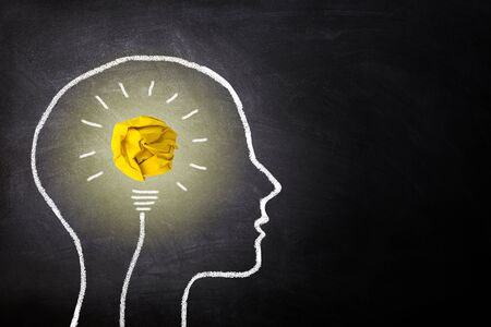 Business Idea Concept : Yellow crumpled paper ball light bulb lighting grow in brain white chalk doodle on chalkboard.