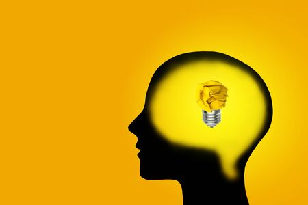 Business Ideas and Creativity Concept : Yellow crumpled paper ball light bulb lighting grow in brain.