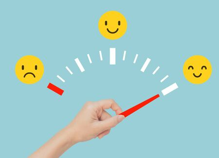 Customer Feedback Concept : Hand holding red gauge and pointing to face emotional in happiness on emotional gauge.