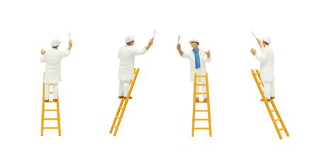 Miniature figure people character as painter standing on wooden ladder and posturing in painting wall with paint tools isolated on white background.