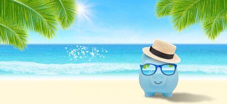 金钱储蓄和旅行旅行概念:蓝色存钱罐穿戴太阳镜和在沙子海滩的织法帽子与海景视图在背景中。