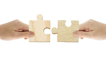 Business Teamwork, Solution and Partnership Concept : Hand holding wooden jigsaw puzzle and combining jigsaw pieces together.