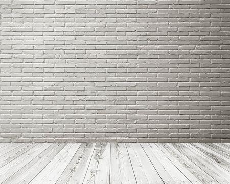 Leerer Raum des Studiozimmers mit weißer Backsteinmauer und Holzboden.