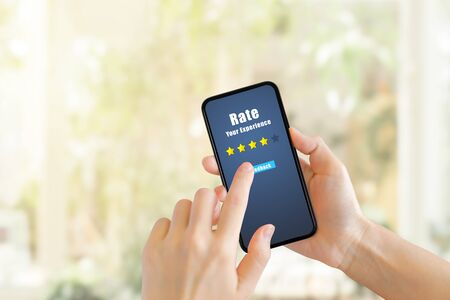 Customer Feedback Concept : Hand pressing feedback button on smartphone for giving best service ranking with blurred cafe restaurant or coffee shop in background.
