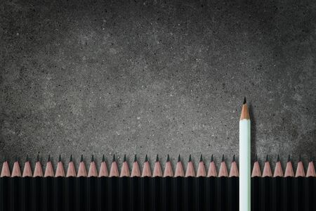 Business Leadership Concept : White pencil standing out from row of many black pencils on concrete background. Foto de archivo - 150367300
