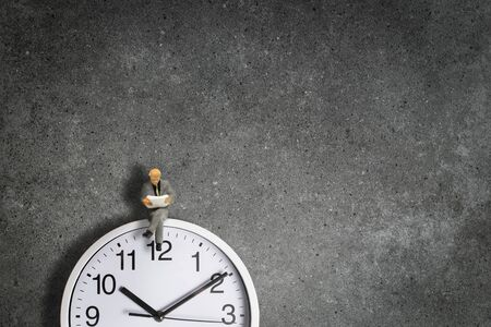 Time Management Concept : Miniature as businessman sit on the top of wall clock and reading a newspaper. Archivio Fotografico