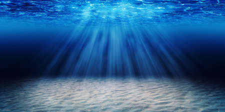 Abstract image of Tropical sand beach on the bottom of underwater dark blue deep ocean wide nature background with rays of sunlight.