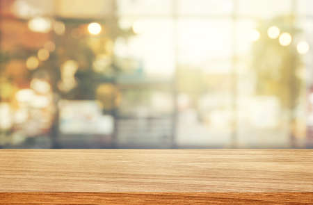Empty wooden table with abstract blurry image of coffee shop or cafe restaurant in background for product showing and advertising. 免版税图像