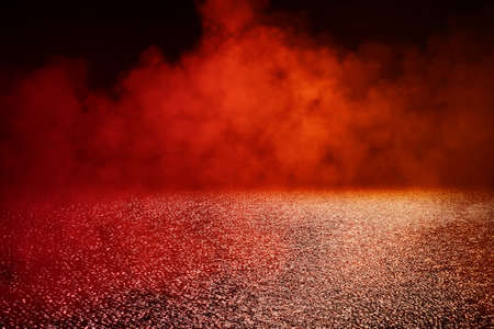 Abstract image of Empty wet asphalt road with red lighting effect and fog or mist in dark background.