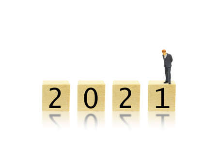 Business and 2021 New Year Concept : Miniature as businessman bend down to look at 2021 wording text on wooden blocks.