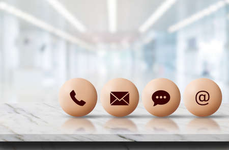 Call Center and Contact US Concept : Contact icon symbols put on marble stone table top with blurry image of inside building in background.